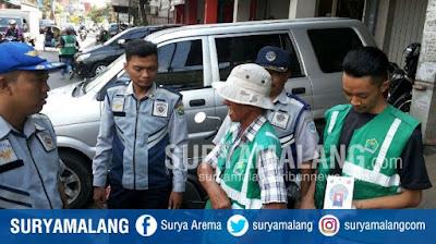 Petugas parkir yang terdaftar/benar di Kota Malang menggunakan rompi hijau + ada no. identitas di bagian belakang (suryamalang.tribunnews.com)
