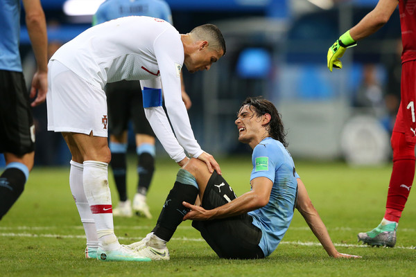 Cristiano Ronaldo of Portugal helps Edinson Cavani of Uruguay after he goes down injured during the 2018 FIFA World Cup Russia Round of 16 match between Uruguay and Portugal at Fisht Stadium on June 30, 2018 in Sochi, Russia.