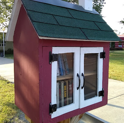 Cabinet of books, mounted outdoors on a post and designed to look like a little building. The cabinet has red siding and a roof covered with green shingling. Through glass doors that are framed in white-painted wood, two shelves of books are visible.