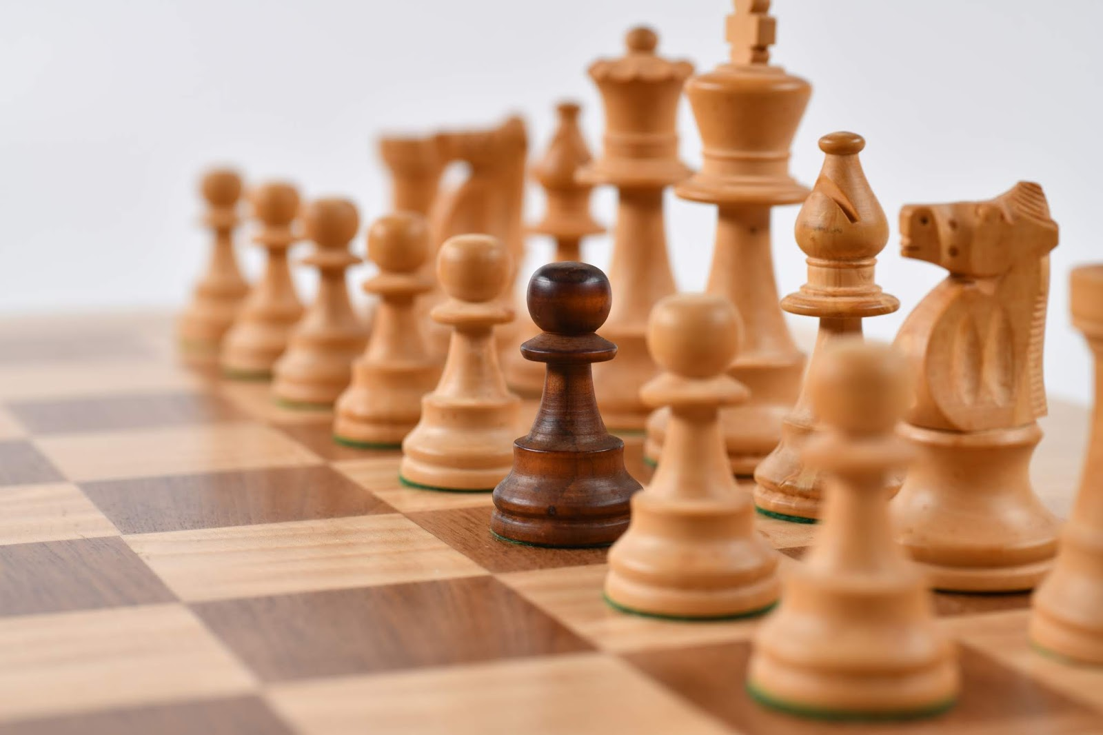 A close up of a beige and brown wood chessboard, focusing on the white/beige pieces, but instead there is one black/brown pawn where a white/beige pawn should be