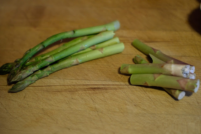 Cutting the woody end off of the asparagus.