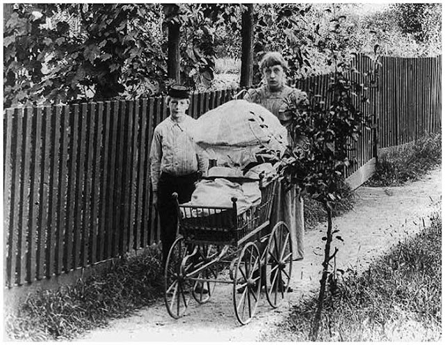 Young boy with girl pushing baby carriage, Staten Island, New York, 1900