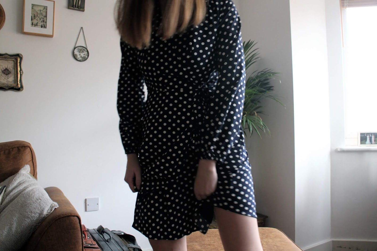 Blogger standing in spotty dress, blurred picture in movement