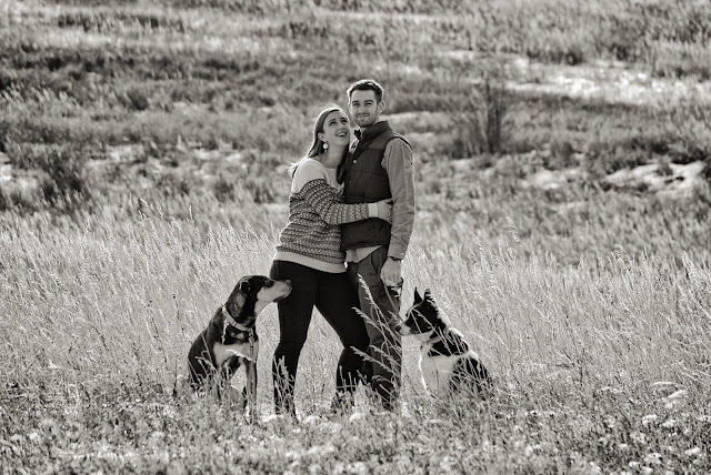 a young woman looks up to her fiance as he looks to the camera during an engagement session in Boulder Colorado