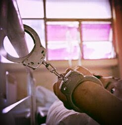 Handcuffed wrist secured to a hospital bed with a mans face looking back at his hand.