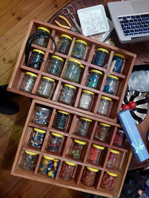 30 Gläschen mit verschiedenfarbenen Perlen in Schubladeneinsätzen