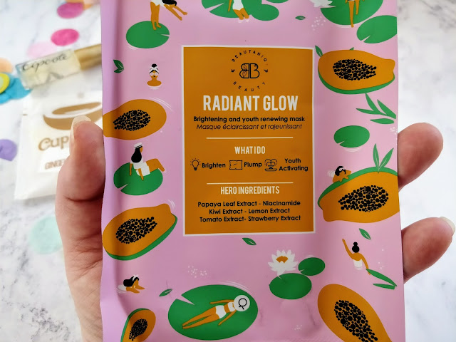 Hand holding a the Radiant Glow Face Mask, the packaging covered in a fruit and lady print