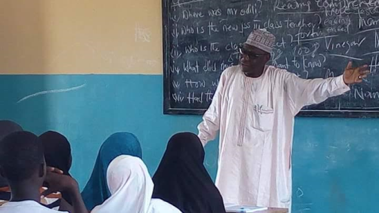 A Local Government Chairman Is Pictured Teaching Primary School Pupils In Borno State