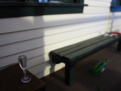 Early-morning shot of a one-twelfth scale model school veranda, with a school chair with an empty wine glass on its seat and a bench with a toppled glass on it and an empty wine bottle under it.