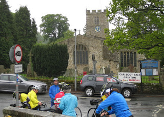 Cyclists pause across from St. Andrew's Church, Grinton, Yorkshire Dales, England