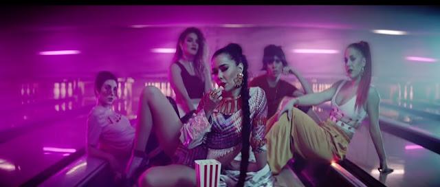 Vemos en una bolera a Beatriz Luengo comiendo palomitas, detrás 4 bailarinas
