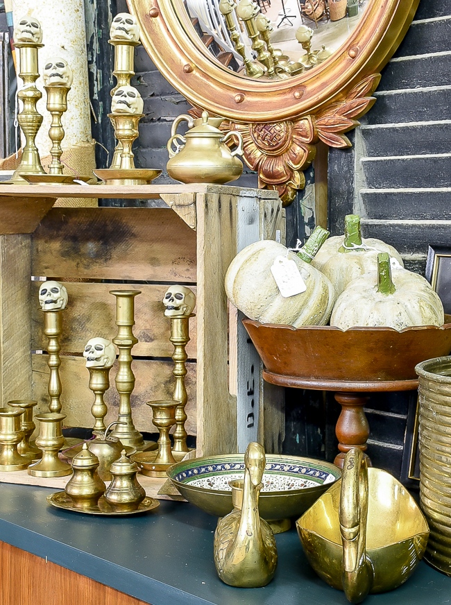 Brass candlesticks topped with skulls and cement pumpkins