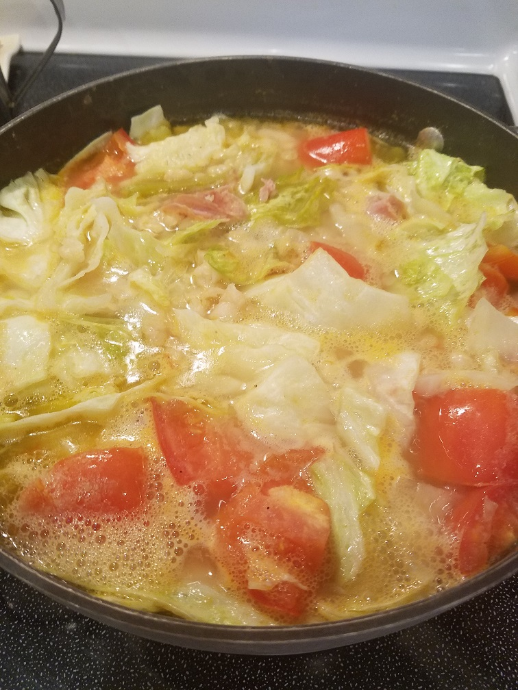 This is a ham cabbage and white bean comfort soup. It has tomatoes, carrots and ham and vegetables all on top of stove in one pot