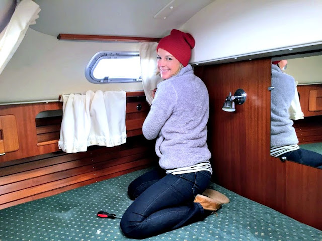 Sara removing Hallberg-Rassy 37 sailboat curtains for cleaning
