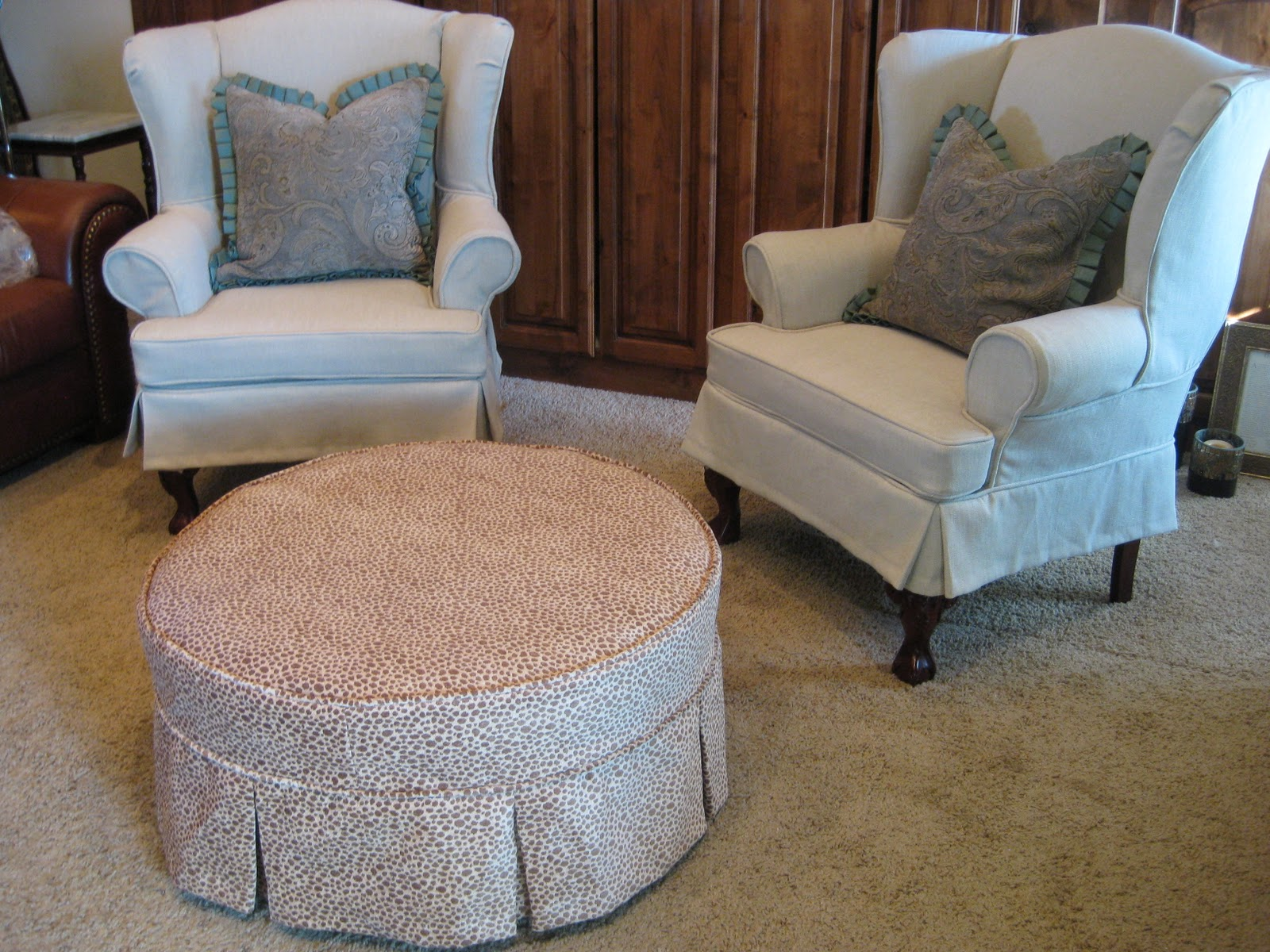 pair of wingbacks and a round ottoman
