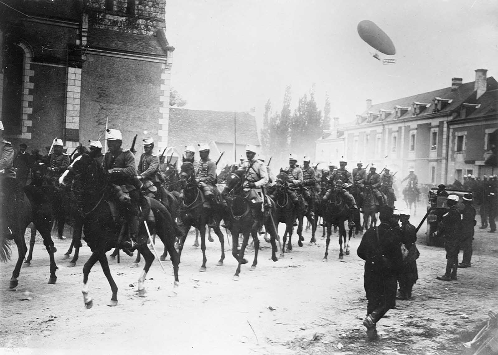French soldiers on horseback in street, with an airship