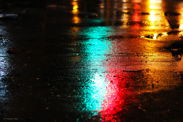 A Minimalist Photo of the Reflection of multi-colored street lights on a rain drenched road late evening.