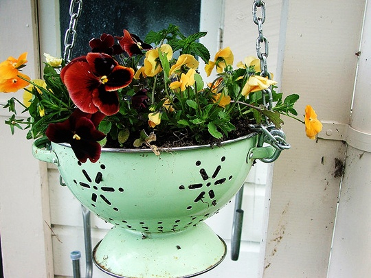 an old colander makes for a great hanging planter for the front porch