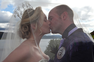 Just married couple kissing under a bridal veil. Bride has chosen a tall tiara for her wedding day look
