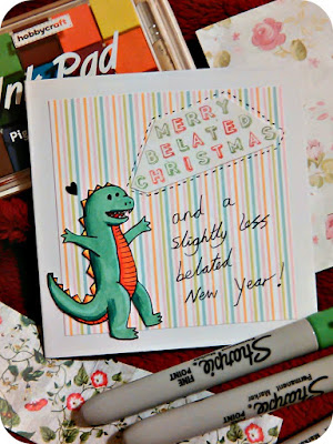 """Merry belated christmas and a slightly less belated new year"" card with a dinosaur on it."
