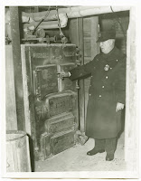 Investigating cause of nine deaths. Chief of police Dennis J. Hullisey of Hanover, N. H., shown inspecting the boiler in the cellar of the Theta Chi fraternity house where nine students were killed by carbon monoxide poisoning the night of February 25. Investigation revealed that a slight explosion in the furnace had broken the flue pipe and allowed the gas to penetrate the basement and the upper floors of the house, killing nine Dartmouth College Students in their sleep. 2-26-34. Associated Press Photo From New York please use credit.