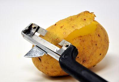 Tarta de papa. Pelapapas pelando una papa o patata