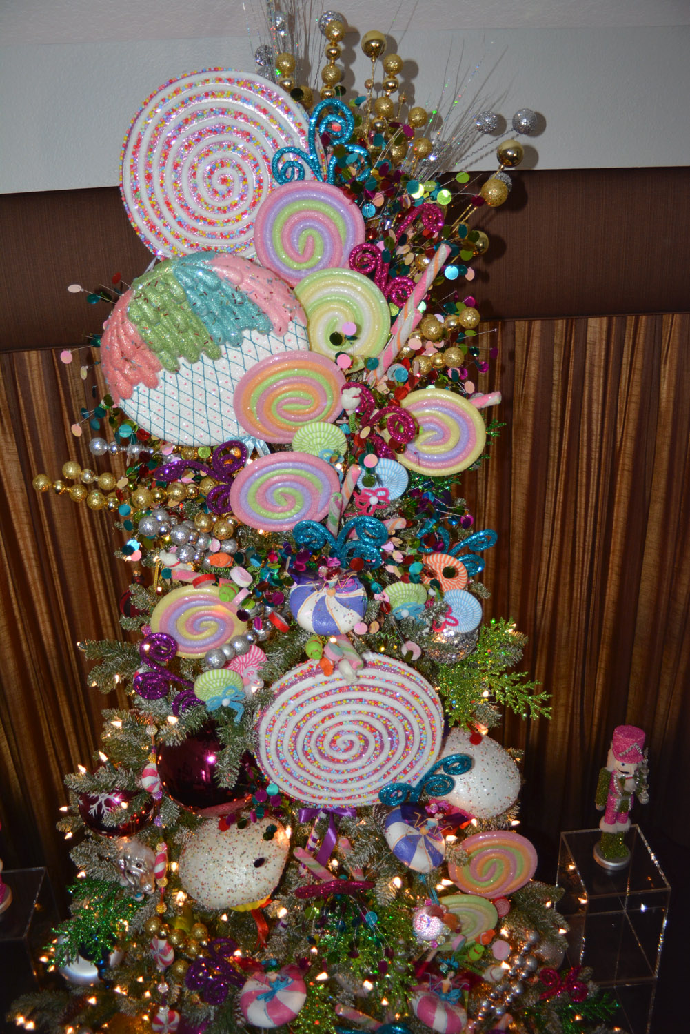 we used lots of bright colors gold and silver picks glitter swirls colorful balls and giant lollipop ornaments to made this christmas tree come to life