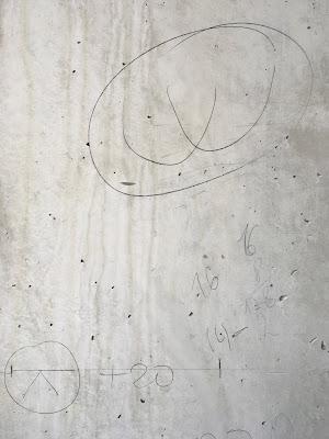 Betonwand mit Zahlen und Zeichen