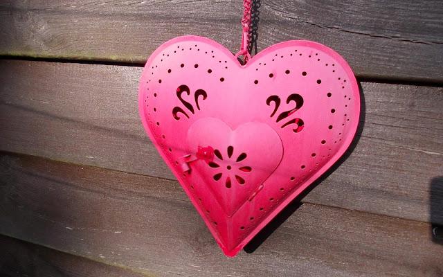 Rood liefdes hartje van metaal aan een houten schutting