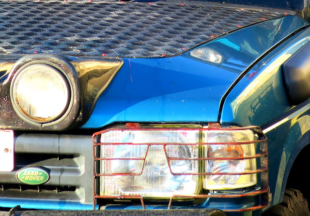Headlight, sidelights and bonnet of blue Land Rover