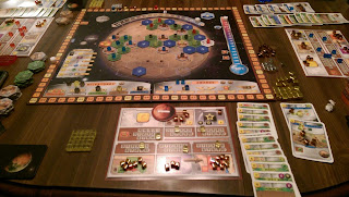 A game of Terraforming Mars in progress. The board is an image of Mars covered in a hexagonal grid with hexagonal tiles representing greenery, cities, and oceans arranged on them, and all but the ocean tiles have a coloured cube on them. There is a track from 0 to 14 represnting the atmospheric oxygen content at the top, and a thermometer running from -30º C to 8º C along the right side. A scoring track runs around the outer edge of the board. Player mats can be seen around the board, as well as tableaus of played cards and the various cubes: some in the players' colours and some in gold, silver, and bronze.