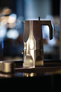 Alessi Ossidiana Stovetop Espresso Maker sitting on a table with blurry lights in the background