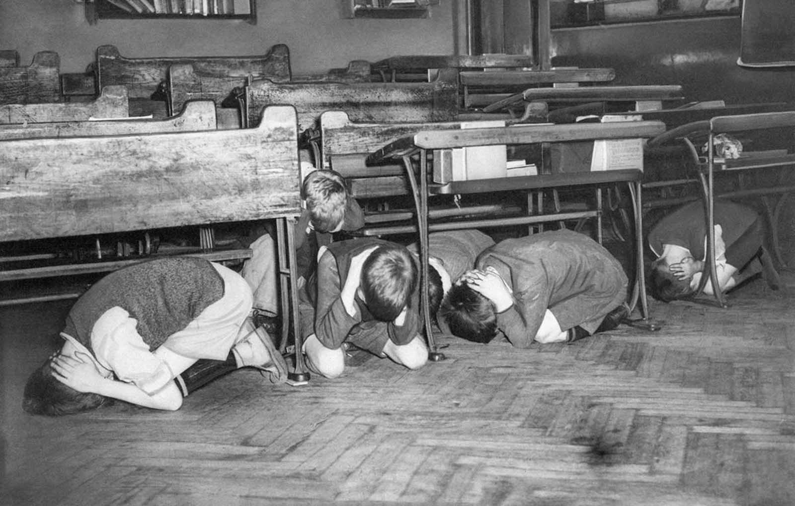 These London schoolchildren are in the midst of an air raid drill ordered by the London Board of Education as a precaution in case an air raid comes too fast to give the youngsters a chance to leave the building for special shelters, on July 20, 1940. They were ordered to go to the middle of the room, away from windows, and hold their hands over the backs of their necks.