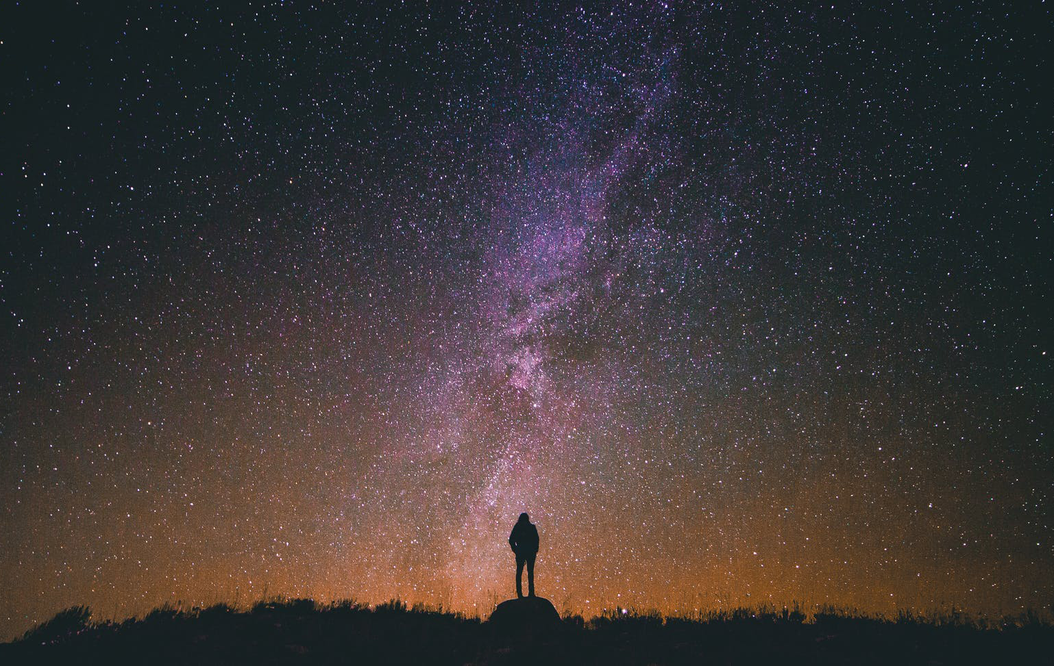 figure standing under a starry night sky observing the universe
