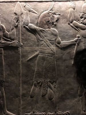Assyrian stone relief showing lion headed man