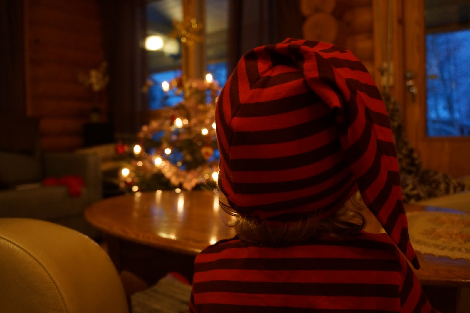 toddler wearing finnish marimekko elf hat in front of a christmas tree