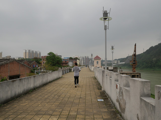 man jogging on a wall bordering the Gui River (桂江) in Wuzhou (梧州)