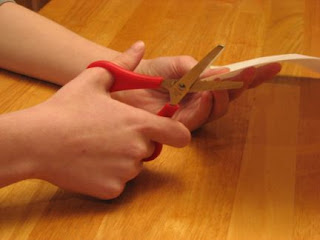 Both hands work together to cut paper and perform other skills