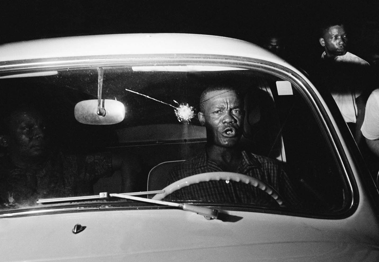 Ivory Ward, 43, sits in his car, with a hole in his windshield that he said was made by a bullet fired from a truck driven by white men, after African Americans marched in an integration demonstration, June 10, 1964, in St. Augustine, Florida.