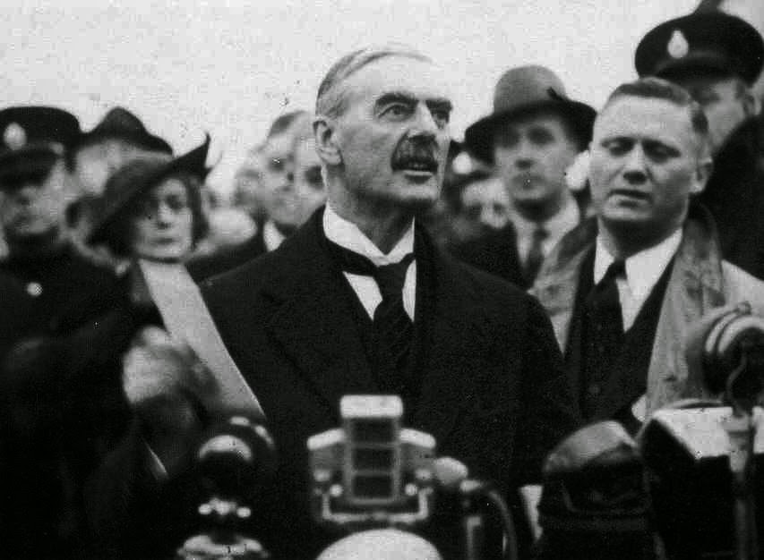 Descendo do avião o premier britânico Neville Chamberlain exibe como um vitória o tratado da capitulação em Munich (1938), grande prólogo da mais mortífera guerra mundial