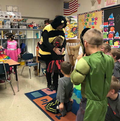 Teacher dressed as a bee hugging a young girl