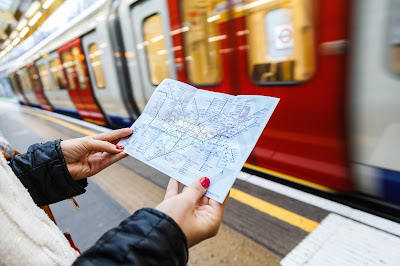 Pic of lady's hands holding small London tube map on platform as tube passes
