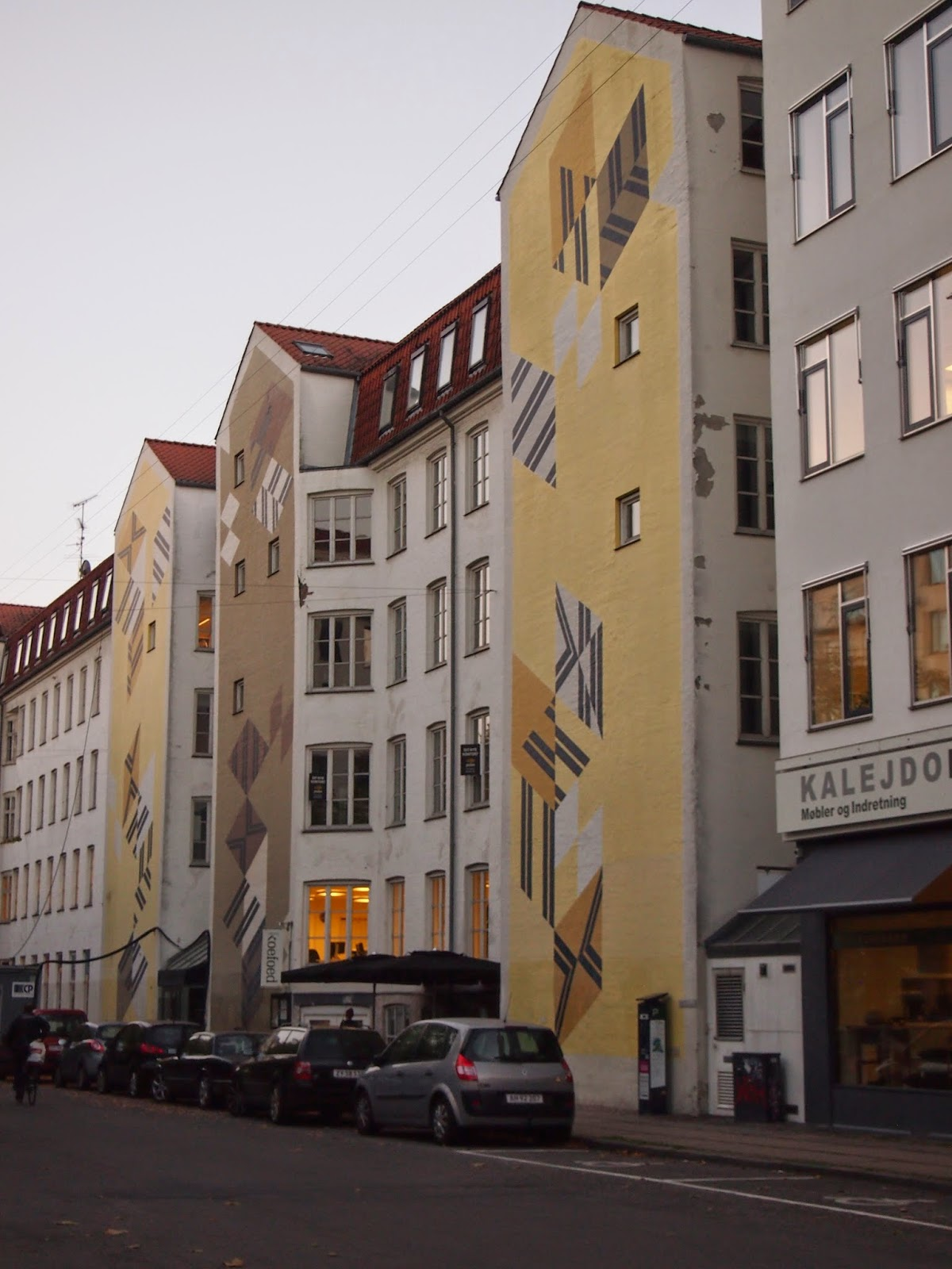 three sets of street art on the sides of a white building in copenhagen