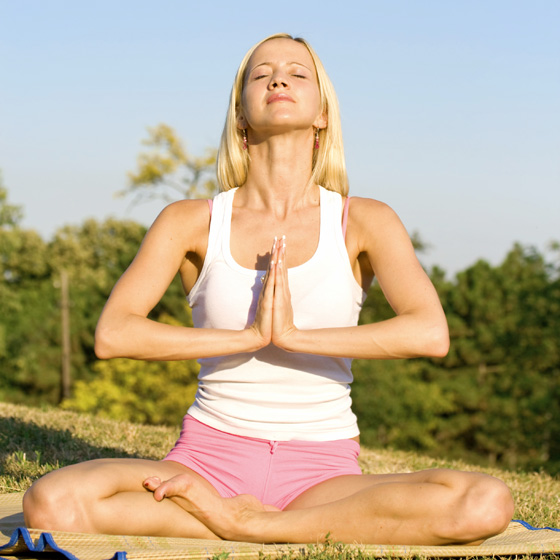 Young woman doing yoga (meditation) in the meadow