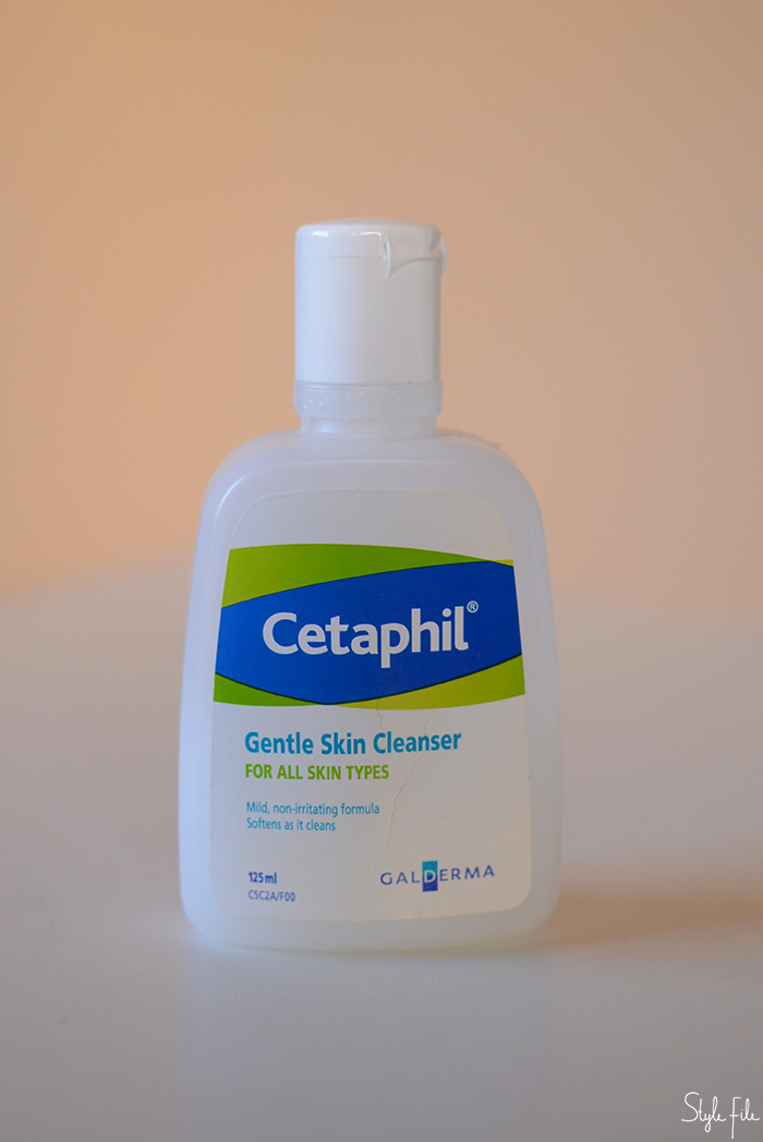 An image of Cetaphil gentle skin cleanser in a white bottle in front of a peach background for a beauty review