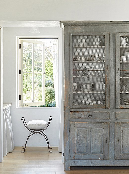 Chicken wire detail on a door of a French antique painted cabinet in a #farmhousekitchen by #BrookeGiannetti