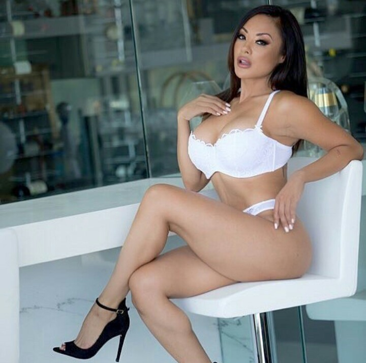 Kaylani Lei in white Pant, white bra and black shoe, sitting