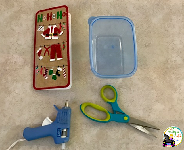 A holiday greeting card, an empty plastic container, a glue gun, and scissors
