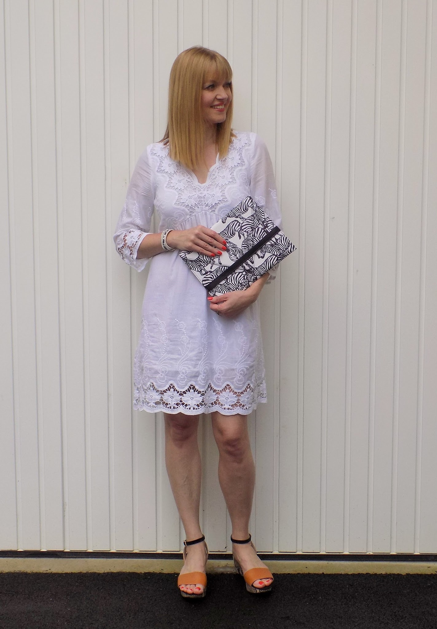 White lace dress, zebra print clutch bag, leopard print wrap bracelet and wedge sandals
