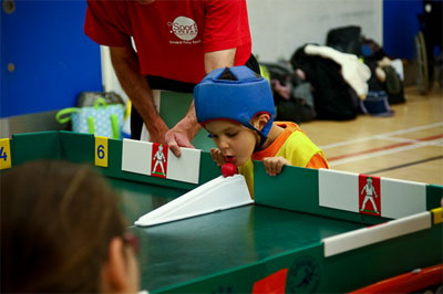 Image of a young child about to bowl using their chin, in table cricket.